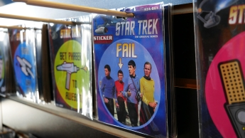 """...oder Sticker, die auf eine Star Trek-Eigenart hindeuten. Denn immer wenn ein unbekanntes Mitglied die bekannten Charaktere auf einer Außenmission begleitet, kann man sicher sein, dass dieser recht bald das Zeitliche segnet. Schiffsarzt Dr. """"Pille"""" McCoy diagnostiziert dann meist: """"Er ist tot, Jim!"""""""